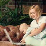 Madre joven que trabaja en casa con el bebé fotografía de archivo