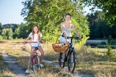 Madre joven que va a merendar en el campo con la hija en las bicicletas Imágenes de archivo libres de regalías