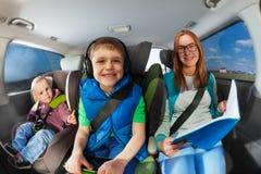 Madre joven que viaja en coche con dos niños fotografía de archivo