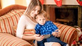 Madre joven sonriente con sus historietas de observación del hijo que se sientan en butaca en la sala de estar fotos de archivo