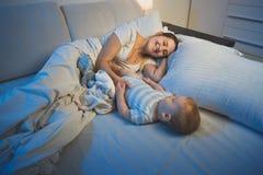 Madre joven sonriente feliz que miente en cama con sus 9 meses del hijo del bebé en la noche Foto de archivo