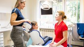 Madre joven sonriente que habla con el dentista pediátrico en oficina del dentista Fotos de archivo libres de regalías