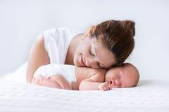 Madre joven y bebé recién nacido en el dormitorio blanco Foto de archivo libre de regalías