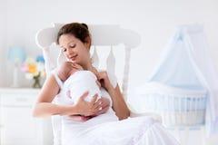 Madre joven y bebé recién nacido en el dormitorio blanco Fotos de archivo libres de regalías