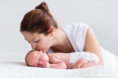 Madre joven y bebé recién nacido en el dormitorio blanco imagen de archivo libre de regalías
