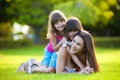 Madre joven y dos hijas que juegan al aire libre fotografía de archivo libre de regalías