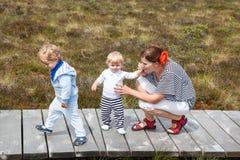 Madre joven y dos niños pequeños en parque de naturaleza del verano imagen de archivo libre de regalías