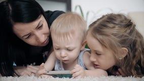 Madre joven y dos niños que se divierten con la tableta en el piso en casa, forma de vida almacen de metraje de vídeo