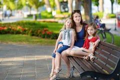 Madre joven y dos pequeñas hermanas lindas que se sientan en un banco que abraza en día de verano caliente y soleado Imagen de archivo