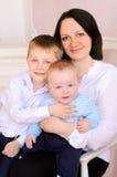 Madre joven y dos pequeños hijos dentro foto de archivo