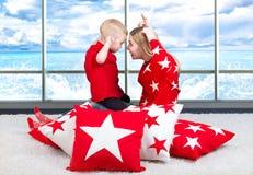 Madre joven y el pequeño jugar del hijo El concepto de un día de fiesta de la familia Almohadas hermosas para adornar el interior imagen de archivo libre de regalías