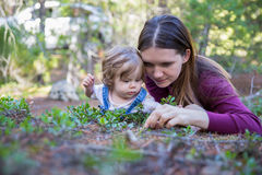 Madre joven y niña pequeña que mienten en la tierra que mira abajo Imágenes de archivo libres de regalías