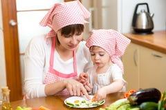 Madre joven y niño que hacen verduras divertidas el plato Foto de archivo libre de regalías