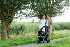 Madre joven y padre que caminan al aire libre con el bebé en cochecito de niño Foto de archivo libre de regalías
