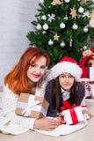 Madre joven y pequeña hija con las cajas de regalo y la Navidad t fotos de archivo