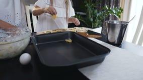 Madre joven y pequeña hija que hacen las galletas en cocina Mujer y niña en la cocina que coloca la pasta de las galletas encendi metrajes