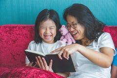Madre joven y pequeña muchacha de la hija que leen un libro en el sofá en fotos de archivo libres de regalías