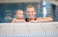 Madre joven y pequeño hijo en una piscina Imagenes de archivo