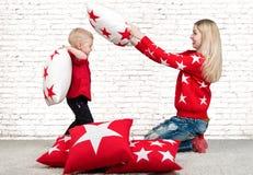 Madre joven y pequeño hijo que juegan con las almohadas, lucha de almohada El concepto de un día de fiesta de la familia Almohada Imagen de archivo libre de regalías