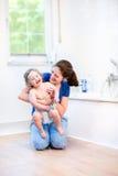 Madre joven y su bebé feliz en cuarto de baño fotos de archivo