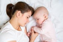 Madre joven y su bebé que duermen junto Foto de archivo