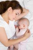 Madre joven y su bebé que duermen junto Fotos de archivo