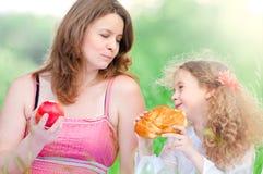 Madre joven y su consumición de la hija Imagen de archivo libre de regalías