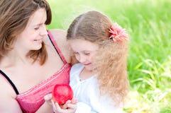 Madre joven y su hija con la manzana Foto de archivo libre de regalías