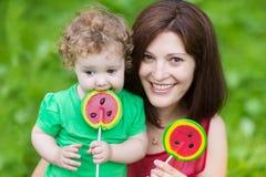 Madre joven y su hija del bebé que comen el caramelo de la sandía Fotografía de archivo