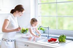 Madre joven y su hija del niño que cocinan la ensalada Fotos de archivo