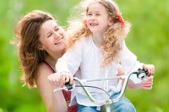 Madre joven y su hija en la bicicleta Fotografía de archivo libre de regalías