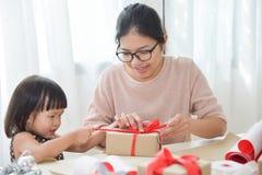 Madre joven y su hija que envuelven una caja de regalo Imagen de archivo