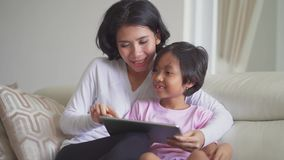 Madre joven y su hija que usa la tableta almacen de video