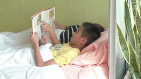 Madre joven y su hijo que leen una historia en dormitorio en casa almacen de metraje de vídeo