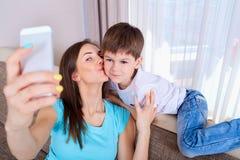 Madre joven y su hijo que toman un selfie en el sofá Fami feliz Foto de archivo
