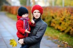 Madre joven y su muchacha del niño en otoño fotografía de archivo libre de regalías