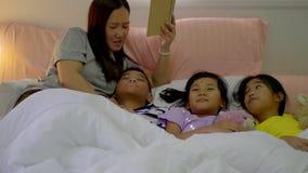 Madre joven y su muchacha e hijo de la hija que leen una historia en dormitorio en casa almacen de video