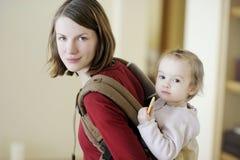 Madre joven y su muchacha en un portador de bebé Imagenes de archivo