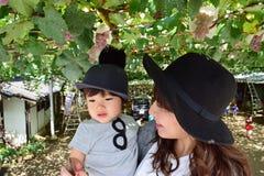 Madre joven y su niño que comen las uvas Imágenes de archivo libres de regalías