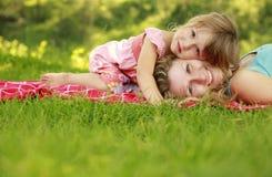 Madre joven y su pequeña hija que juegan en hierba Foto de archivo libre de regalías