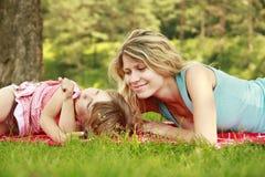 Madre joven y su pequeña hija que juegan en hierba Fotos de archivo