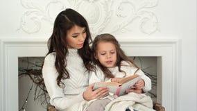 Madre joven y su pequeña hija que leen un cuento de la Navidad que se relaja en una butaca por el lugar del fuego Fotografía de archivo libre de regalías