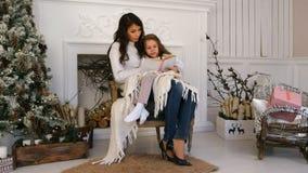 Madre joven y su pequeña hija que leen un cuento de la Navidad que se relaja en una butaca por el lugar del fuego Imagen de archivo