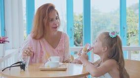 Madre joven y su pequeña hija que pasan tiempo en un café con helado almacen de metraje de vídeo