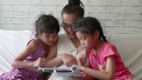 Madre joven y sus muchachas de la hija que leen una historia en dormitorio en casa almacen de metraje de vídeo