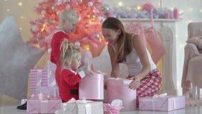 Madre joven y sus niños con los regalos de la Navidad almacen de metraje de vídeo