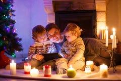 Madre joven y sus pequeños niños que se sientan por una chimenea en C Imagen de archivo libre de regalías
