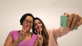 Madre jubilada e hija joven que muestran el signo de la paz y que hacen la foto divertida de Selfie con el teléfono móvil 4K almacen de video