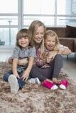 Madre juguetona con los niños que se sientan en la manta en sala de estar Fotografía de archivo libre de regalías