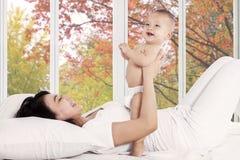 Madre juguetona con su bebé en dormitorio Imagenes de archivo